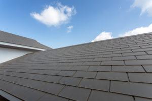 A perfectly laid slate roof sits on a clear, summer day